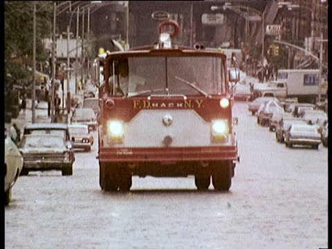 New York City Fire Department trucks drive through street on call out 1970s