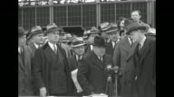 New York City Mayor Fiorello La Guardia standing at microphones on table outdoors WPA Administrator Harry Hopkins standing next to him crowd of...