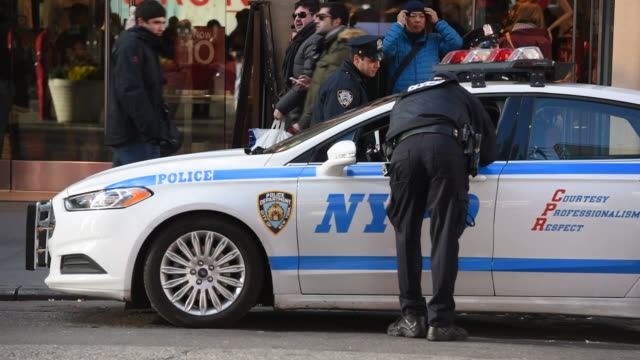 New York City Police Department patrol cars and police officers near Times Square in New York New York US on January 5 Wide shot of an African...