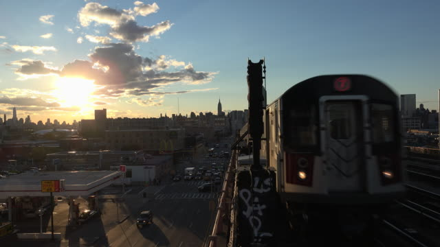 New York City Subway train coming in and out of Manhattan Freedom tower and Empire state buildings are in the background