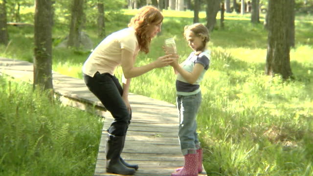 WS, USA, New York State, Bedford Hills, mother and daughter(6-7 years) looking at jar with water sample, walking on boardwalk in forest