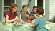 MS, USA, New York State, Bedford Hills, woman with children (6-9 years) painting pots at front of house