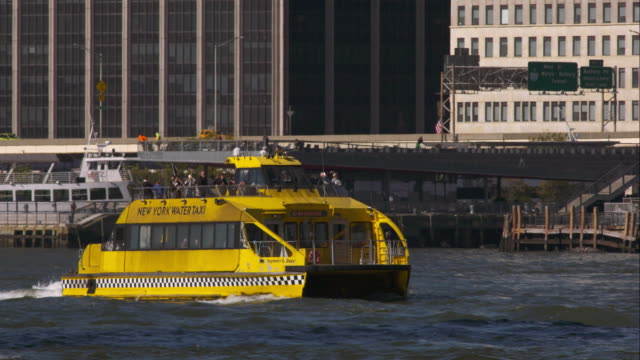 New York Water Taxi moves along Hudson River in front of Westside Highway on a sunny day