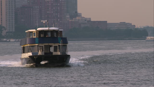 New York water taxi moves along Hudson River toward camera in slow motion.