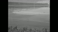 New York Yankees players huddle together with bats touching ground raising bats to shoulders / crowds in stands at Yankee Stadium / Yogi Berra at bat...