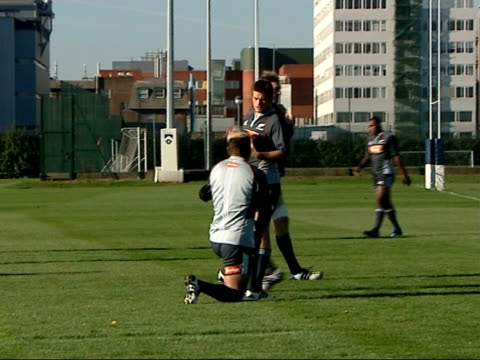 New Zealand's rugby union squad practice ahead of a test match against England More of training session / Captain Richie McCaw talking to kneeling...