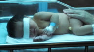 Neugeborene unter UV-Lampe im Inkubator
