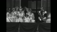 Newly crowned Queen Elizabeth II along with her maids of honor walk out onto balcony at Buckingham Palace with Prince Charles and Princess Anne...