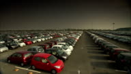 Newly manufactured cars occupy a large parking lot. Available in HD