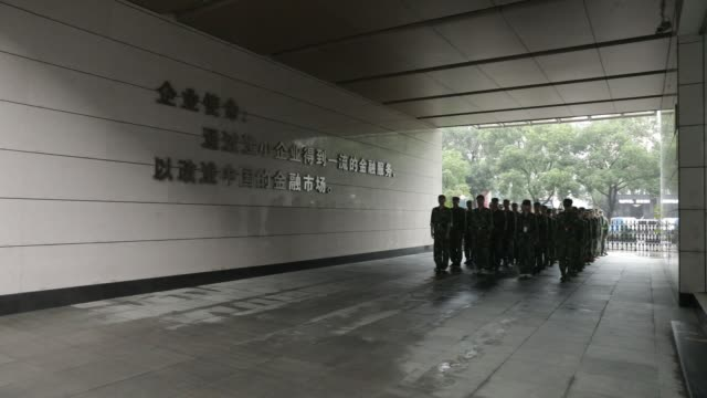 Newly recruited employees dressed in fatigues participate in a militarystyle marching exercise at Bank of Taizhou Co's training facility in Taizhou...