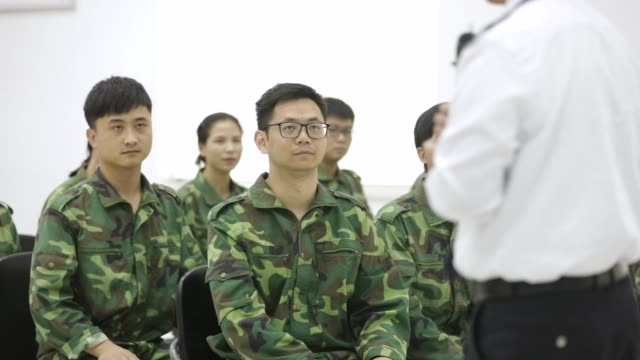 Newly recruited employees dressed in military fatigues participate in a teambuilding session at Bank of Taizhou Co Ltd's training facility in Taizhou...