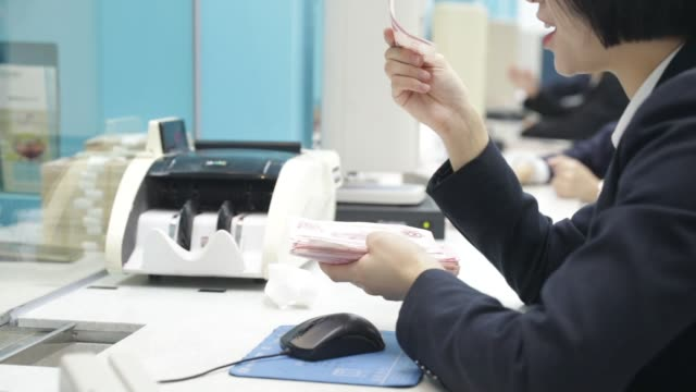 Newly recruited employees sit at teller counters at Bank of Taizhou Co Ltd's training facility in Taizhou China on Tuesday Nov 7 A newly recruited...