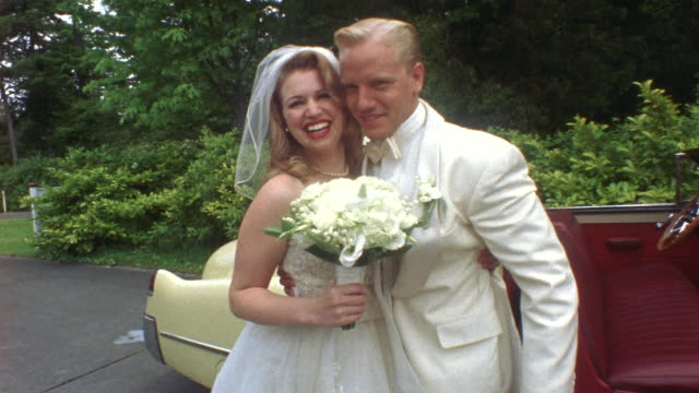 MS Newlywed bride and groom kissing near classic convertible, then groom closes car door / Washington State, USA