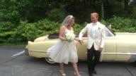 MS PAN Newlywed bride and groom waving and walking past classic convertible / Washington State, USA