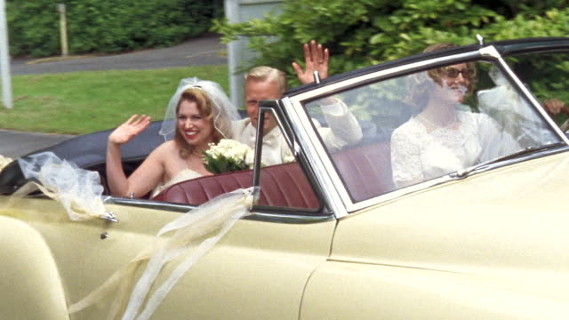 MS PAN Newlywed bride and groom waving in backseat of classic convertible while another woman drives / Washington State, USA