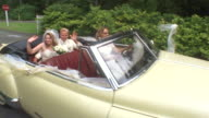 WS PAN Newlywed bride and groom waving in backseat of classic convertible while another woman drives / Washington State, USA