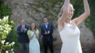 Newlywed bride throwing bouquet to wedding guest