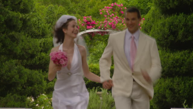 MS newlywed couple running on garden path toward camera / Richmond, Virginia