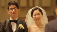 Newlywed Korean couple smiling and bowing with somone