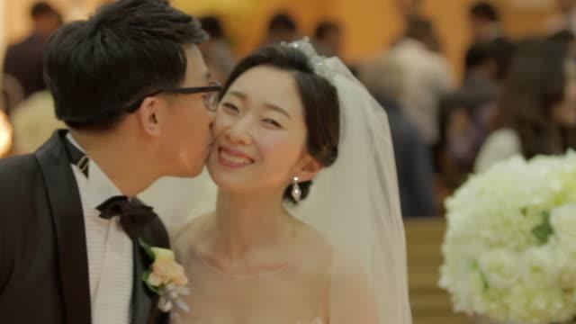 Newlywed Korean groom kissing on the brides cheek