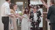 SLO MO Newlyweds being showered with petals when leaving church