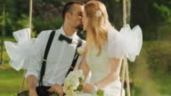 SLO MO LD Newlyweds kissing on a swing