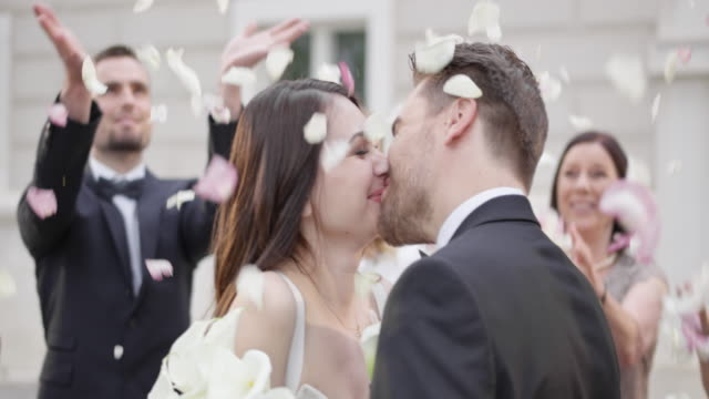 SLO MO Newlyweds kissing while wedding guests throw petals