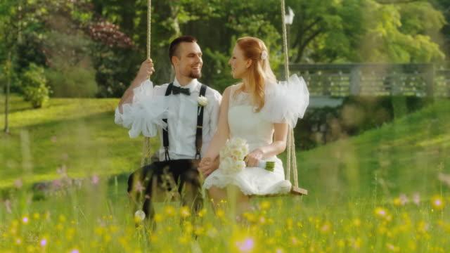 SLO MO DS jonggehuwden zittend op een schommel in de zon