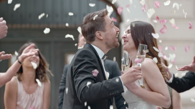 SLO MO Newlyweds toasting and kissing in rose petal shower