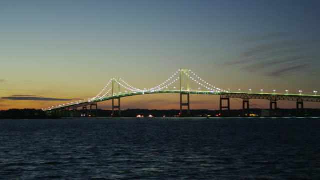 Newport Bridge in a wide shot with bay in the foreground at night.