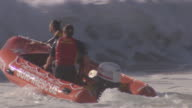 Newport Surf Rescue team pull an inflatable surf rescue rubber dinghy into the rough surf / The Surf Rescue team jump in the dinghy as the waves...