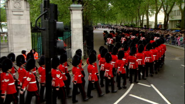 1500 1600 Queen's Guards marching along crowdlined streets Crowds along The Mall
