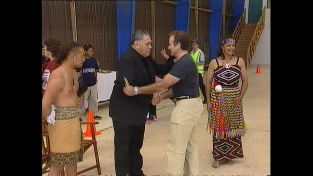 News item about Robin Williams arriving in New Zealand in 1999 and receiving pōwhiri welcome from Māori wearing traditional dress