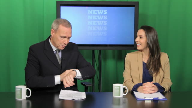 News presenters preparing in television studio for broadcast