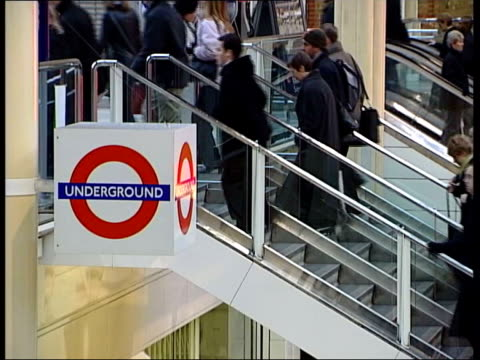 Part one GENERICS TUBE London Liverpool Street INT Underground sign on balcony as commuters people city workers hurrying up stairs Underground sign...