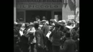Newsboys and men shouting in Italian about second ItaloEthiopian war and distributing papers among crowd / men hoisting flag of Kingdom of Italy with...