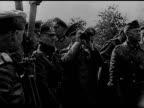 Newspaper headline 'War Starts Warsaw Bombed' WS German artillery firing Hitler holding binoculars bending back to look up TRACKING Silhouette of one...