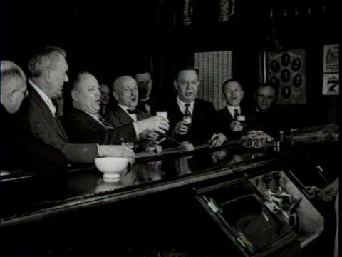 Newsreel / At a bar a group of men sing before they take a drink of beer / another group of bar patrons toast each other and laugh /