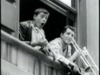 Newsreel / Narrated / A crowd of hundreds of fans gather beneath a building as Jerry Lewis and Dean Martin joke to them from a window / Lewis and...