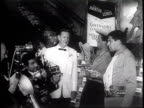 Newsreel / Narrated / A large selection of hats is presented on the staircase in a hotel lobby / Jerry Lewis and Dean Martin fit a large procession...