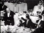 Newsreel / Narrated / At the annual Friars Club dinner Jerry Lewis and Dean Martin interrupt Paramount Pictures president Barney Balaban with jokes...