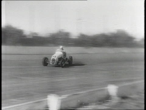 Newsreel / Narrated / Footage of a midget car race on a Milwaukee speedway / A driver loses control of his midget car and crashes into a riverbed /...