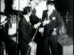 Newsreel /Narrated / Huge crowds wait outside the Paramount Theater in Times Square New York / Jerry Lewis and Dean Martin perform a comedy routine...