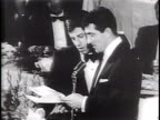 Newsreel / Narrated / Jerry Lewis and Dean Martin jokingly stumble through an acceptance speech in a room full of dinner guests /