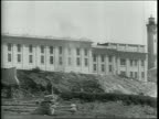 Newsreel / Narrated / Various shots of Alcatraz Island inside and out / Mugshots of the 3 prisoners who tried to escape / Prison guards run around...