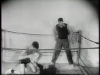Newsreel / Narrated / Wrestling coaches jokingly prepare their fighters in opposite corners of the ring Jerry Lewis and Pierre chimpanzee / Coach...