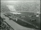 Newsreel / No Audio / 1932 Summer Olympics Closing Ceremonies Los Angeles / Wide shot of closing ceremony with line of men in white uniforms with...