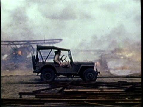 Newsreel / No Audio / Military jeep speeds past burning planes / Camera captures damage from Pearl Harbor attack in 1941 / Planes and debris on fire /