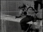 Newsreel / No audio / One worker scoots out onto a beam with no harness / A camera man films him / Arial view of men on beams with New York city in...