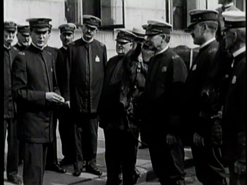 Newsreel / No Audio / Police officers standing in a line with officers on horses standing in the background / Police officer returns his gun to its...